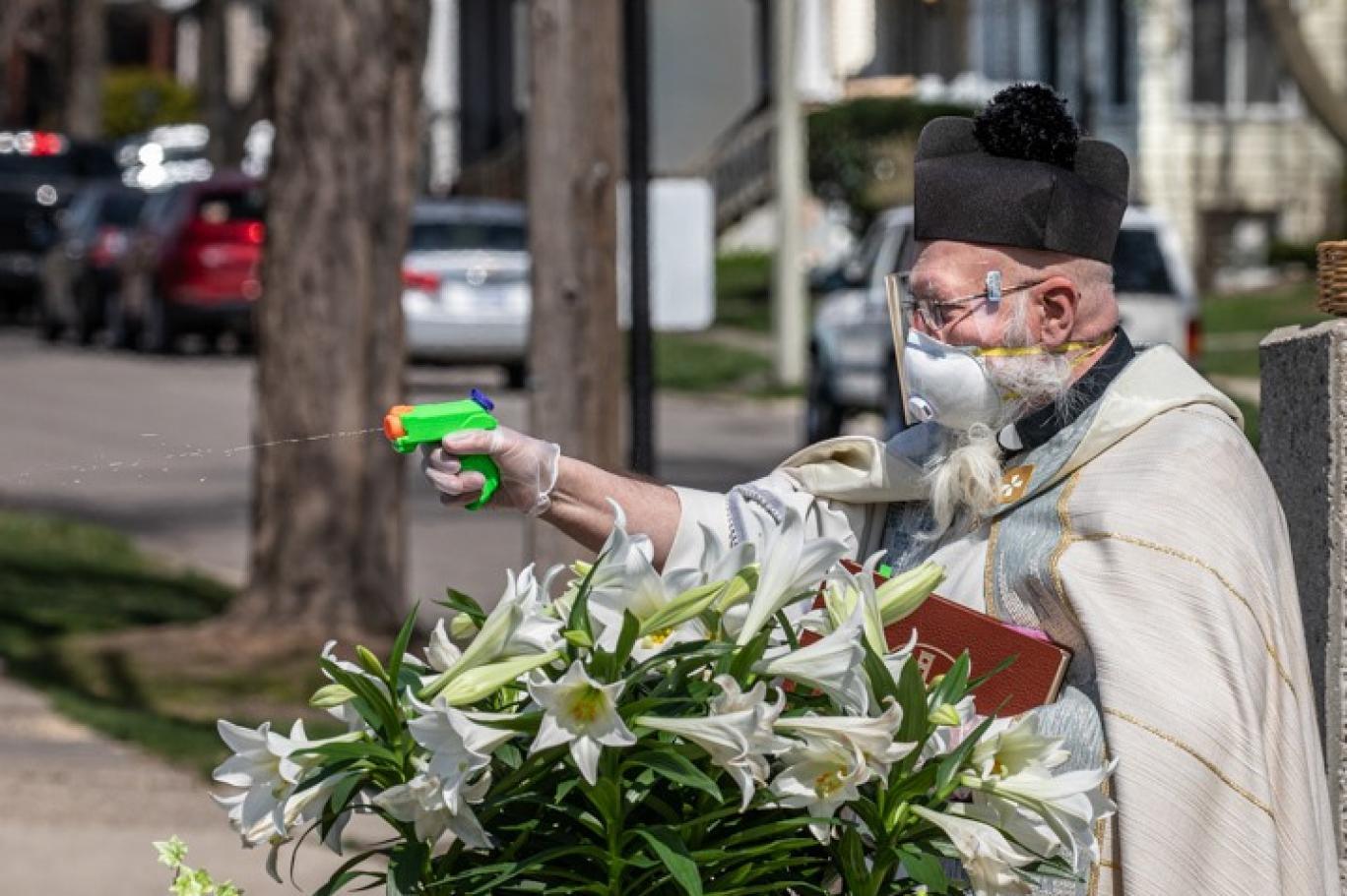 Cemaatine su tabancasıyla kutsal su fışkırtan rahip